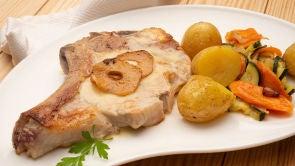 Chuletas de ternera con patatas asadas y verduras salteadas